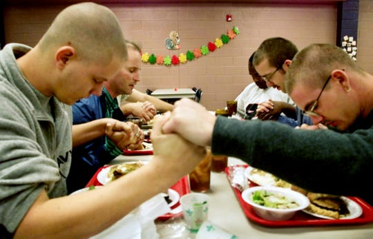 Jason Yohe, left, and Mike Lowks, right, join hands with others staying at the Nashville Rescue Mission and say grace being thankful for their Thanksgiving meal Nov. 22, 2001.