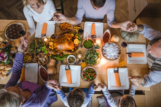 Above View Of Extended Family Saying Grace Before Thanksgiving Dinner