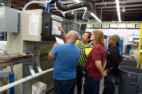 Jose Guillen, second from left, a process engineer at Pelican Wire Company, trains his co-workers on how to use the extruder machine Wednesday, Nov. 21, 2018, in East Naples.
