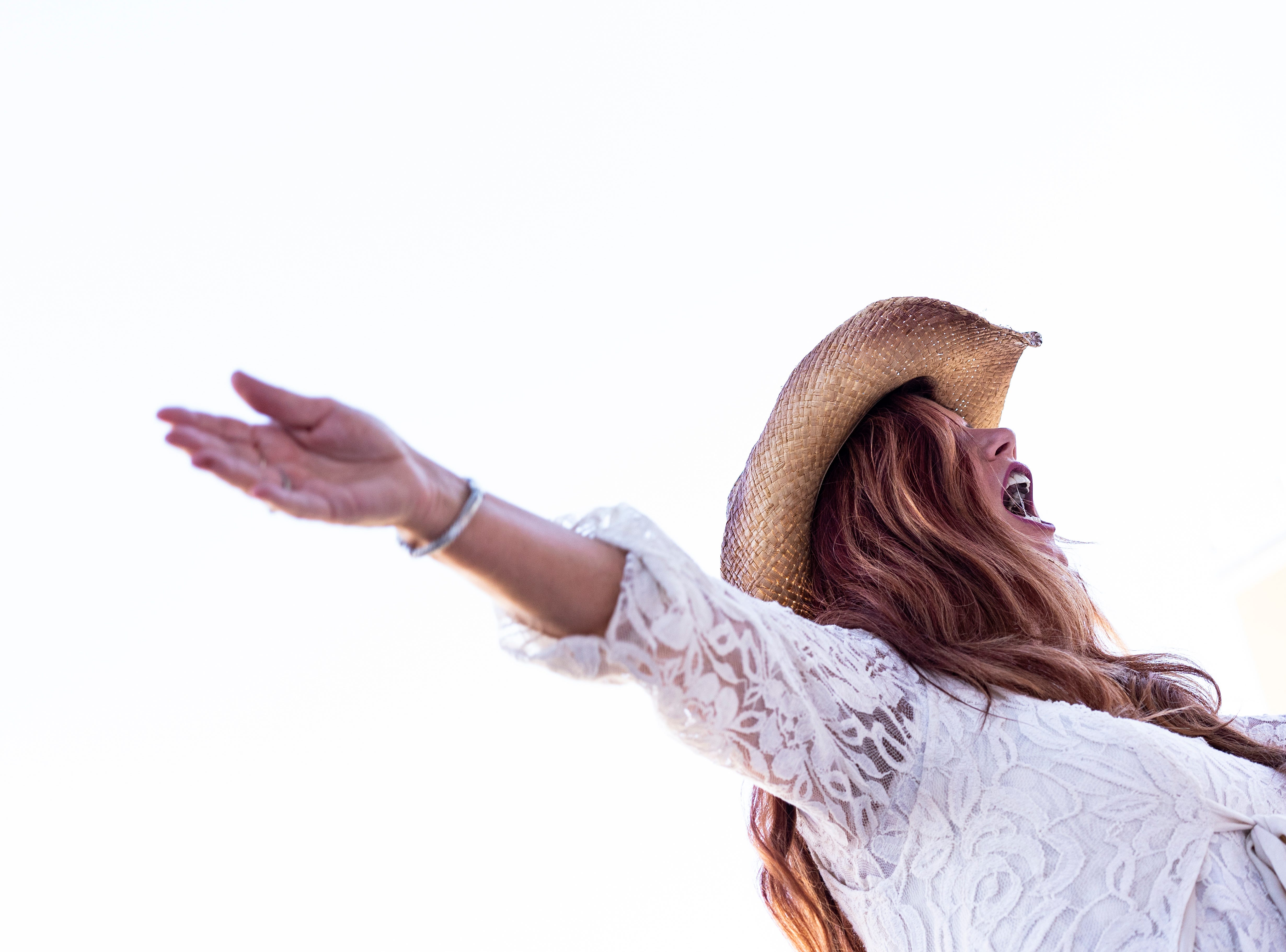 """Valerie Deising, wife of Ben Allen Band bassist Bret Deising, waves her hands in the air while singing along with the band's cover of the song """"Spingsteen"""" by Eric Church at the 63rd annual Farm City BBQ, at theSeminole Casino Hotel on Wednesday, Nov. 21, 2018."""