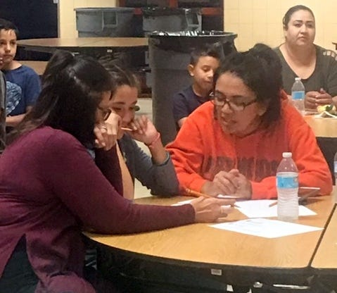 At left, Bataan Elementary School fifth-grade teacher Melissa Noriega, goes over problem solving with students and parents during Math Night at the school.