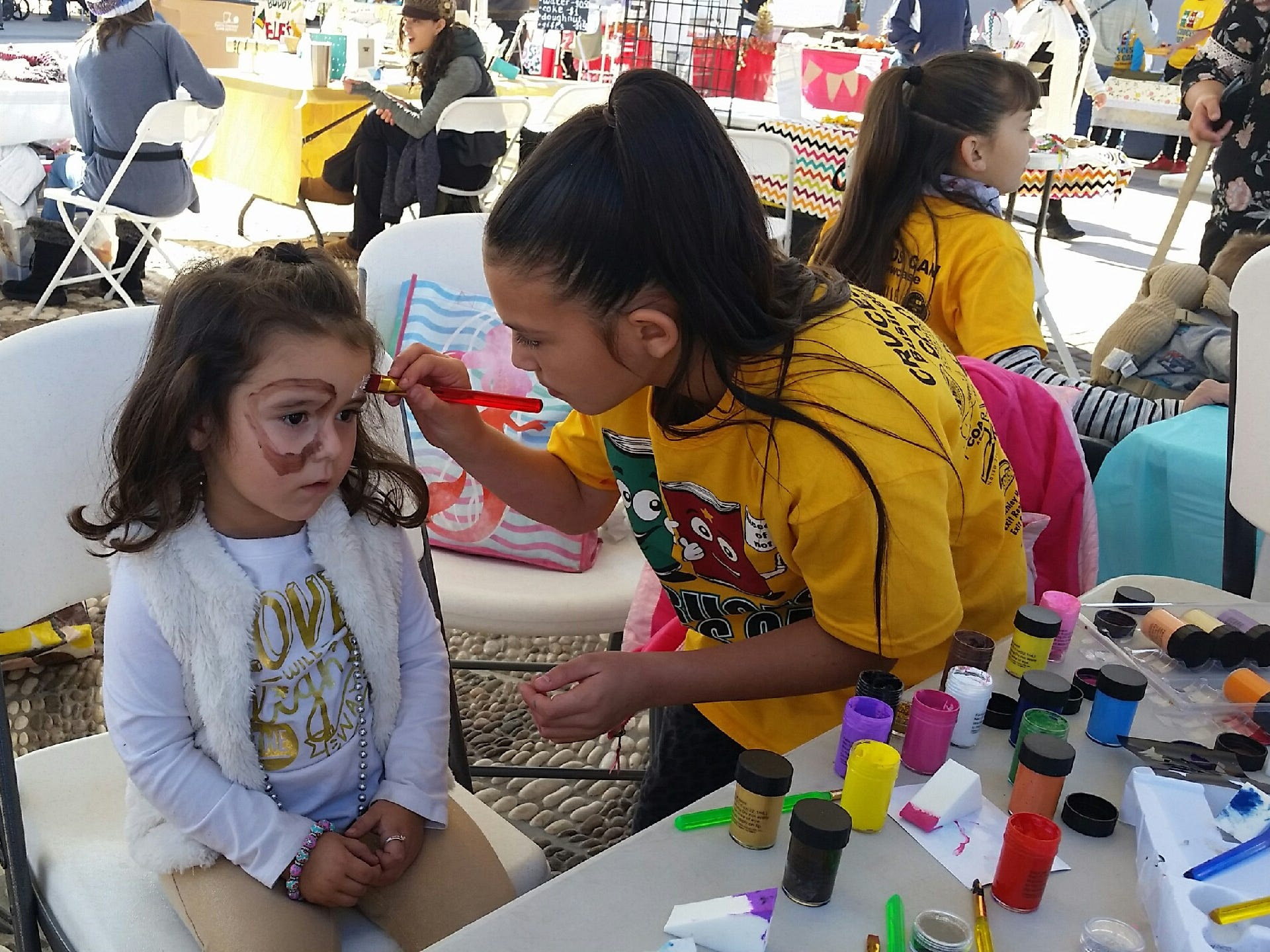 "Alexis Estep, 9, paints a puppy-dog face on 3-year-old customer Jocelyn Perrault of Rio Rancho during the Cruces Kids Can Business Showcase on Saturday, Nov. 17, 2018 in downtown Las Cruces. Estep's business is called ""Magical Faces Face Painting."""