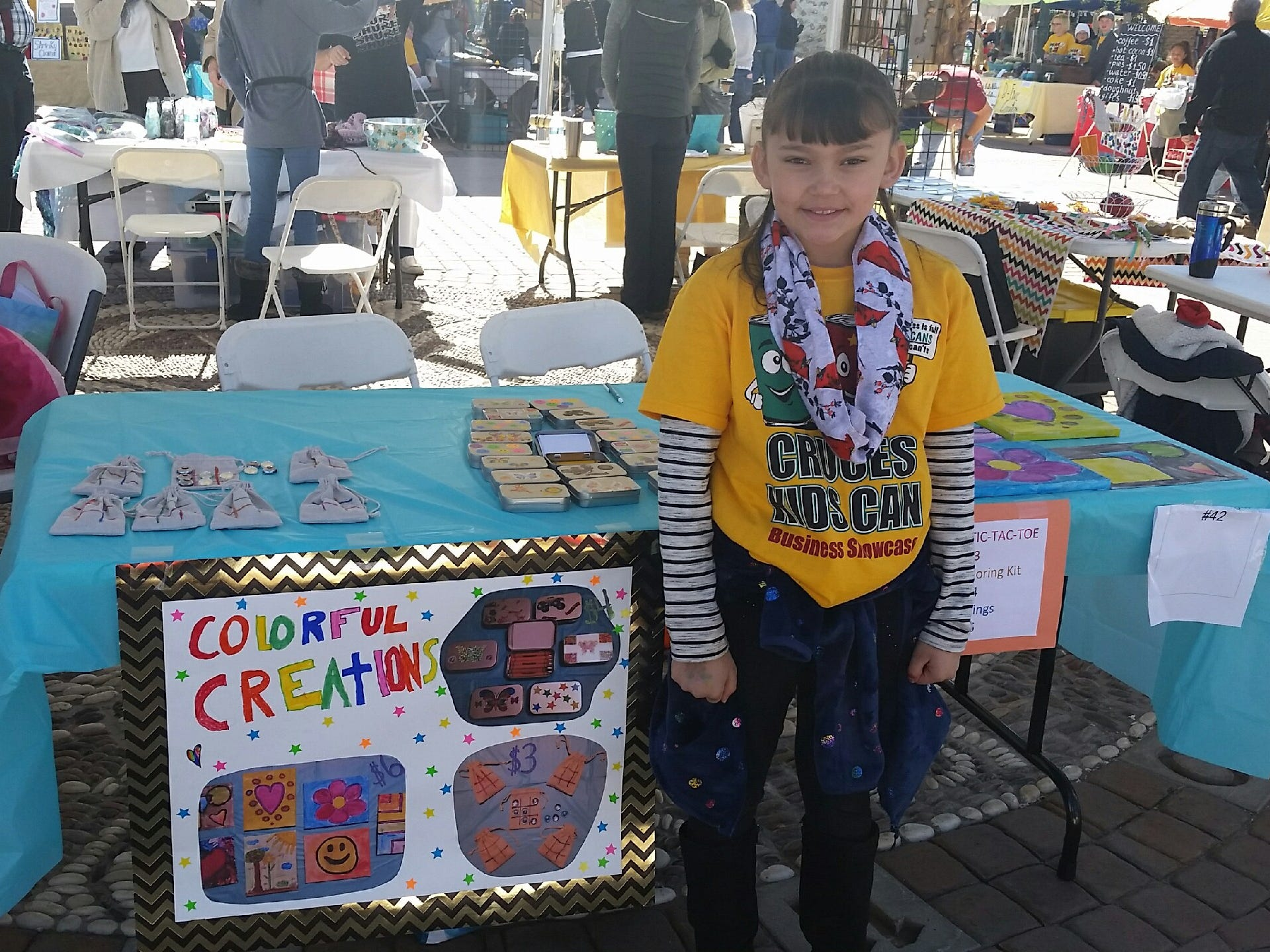 "Analisa Parra, 8, shows off her ""Colorful Creations"" booth during the Cruces Kids Can Business Showcase in downtown Las Cruces on Saturday, Nov. 17, 2018. Parra was selling tic-tac-toe to-go kits, crayon travel kits and her own artwork."