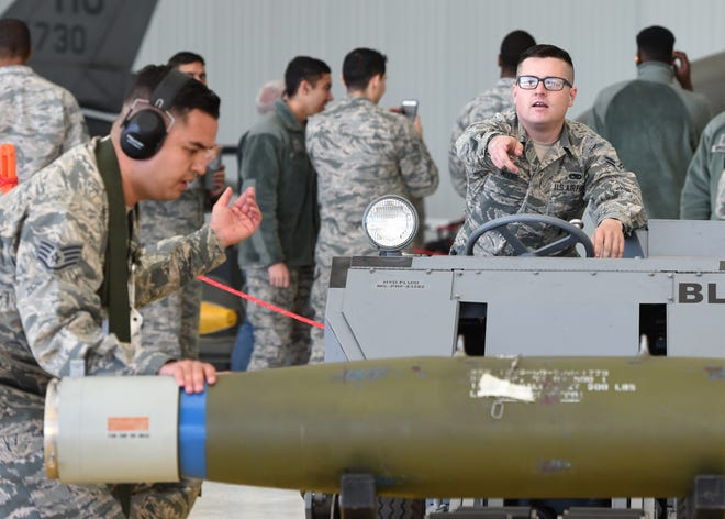 Airman prepare to load an inert bomb on a MQ-9 Reaper during a quarterly load crew competition at Holloman Air Force Base, N.M., November 16, 2018. A total of five aircraft were used to test crews loading skills on F-16 Fighting Falcons and MQ-9s.