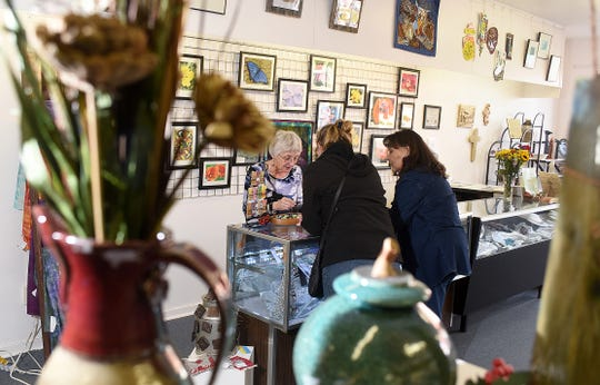 Sue Johnson, left, rings up a purchase for Rebecca Brandt, center, and Karla Montoya during Small Business Saturday on Nov. 26, 2016 at the Three Rivers Art Center in downtown Farmington.