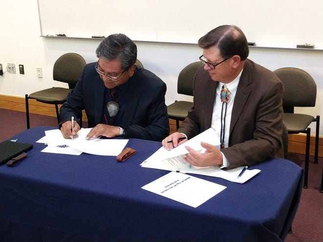 Navajo Nation President Russell Begaye, left, and New Mexico State Land Commissioner Aubrey Dunn sign closing documents for the land exchange on Nov. 16 in Albuquerque.