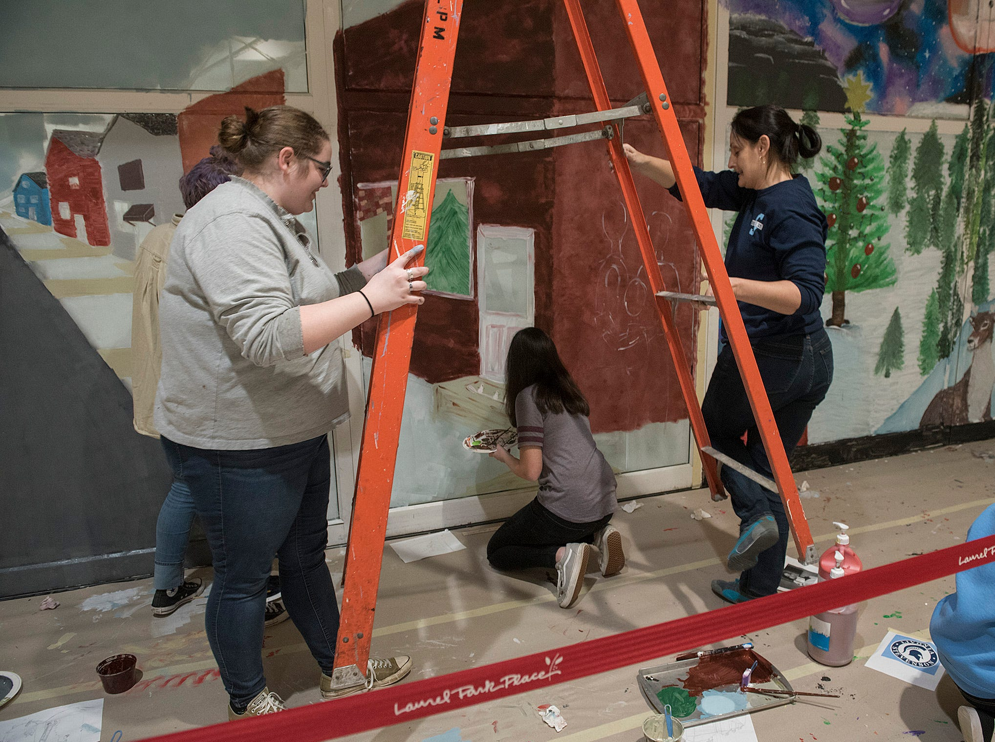 Meghan McQuiston and art teacher Heidi Posh move a ladder into place, carefully avoiding Emily Dobao.