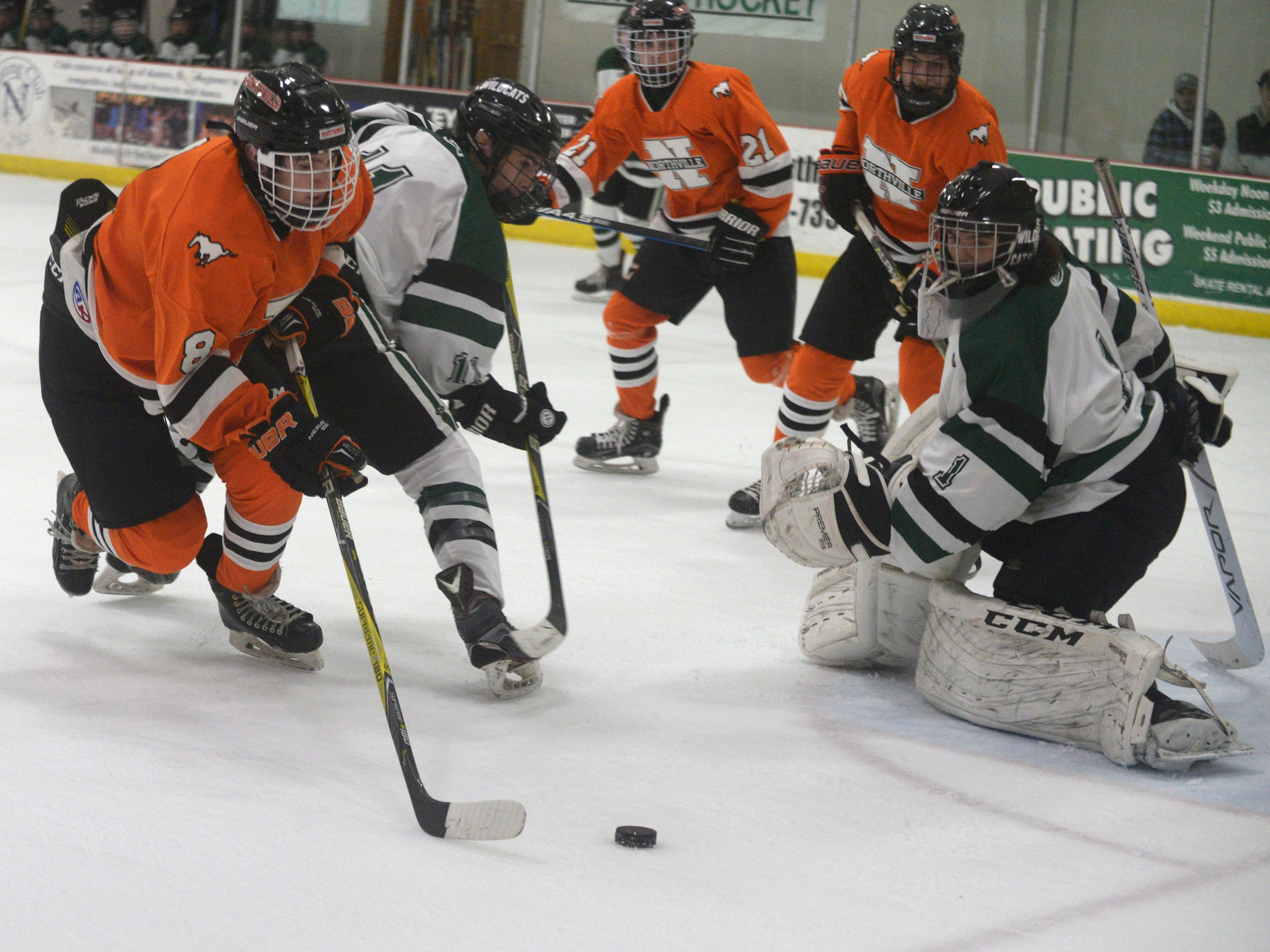 Northville forward Spencer Ziparo (8) and Novi defenseman Mike Small (11) and goalie Evan Budd (1) during a KLAA West match up between the rivals.