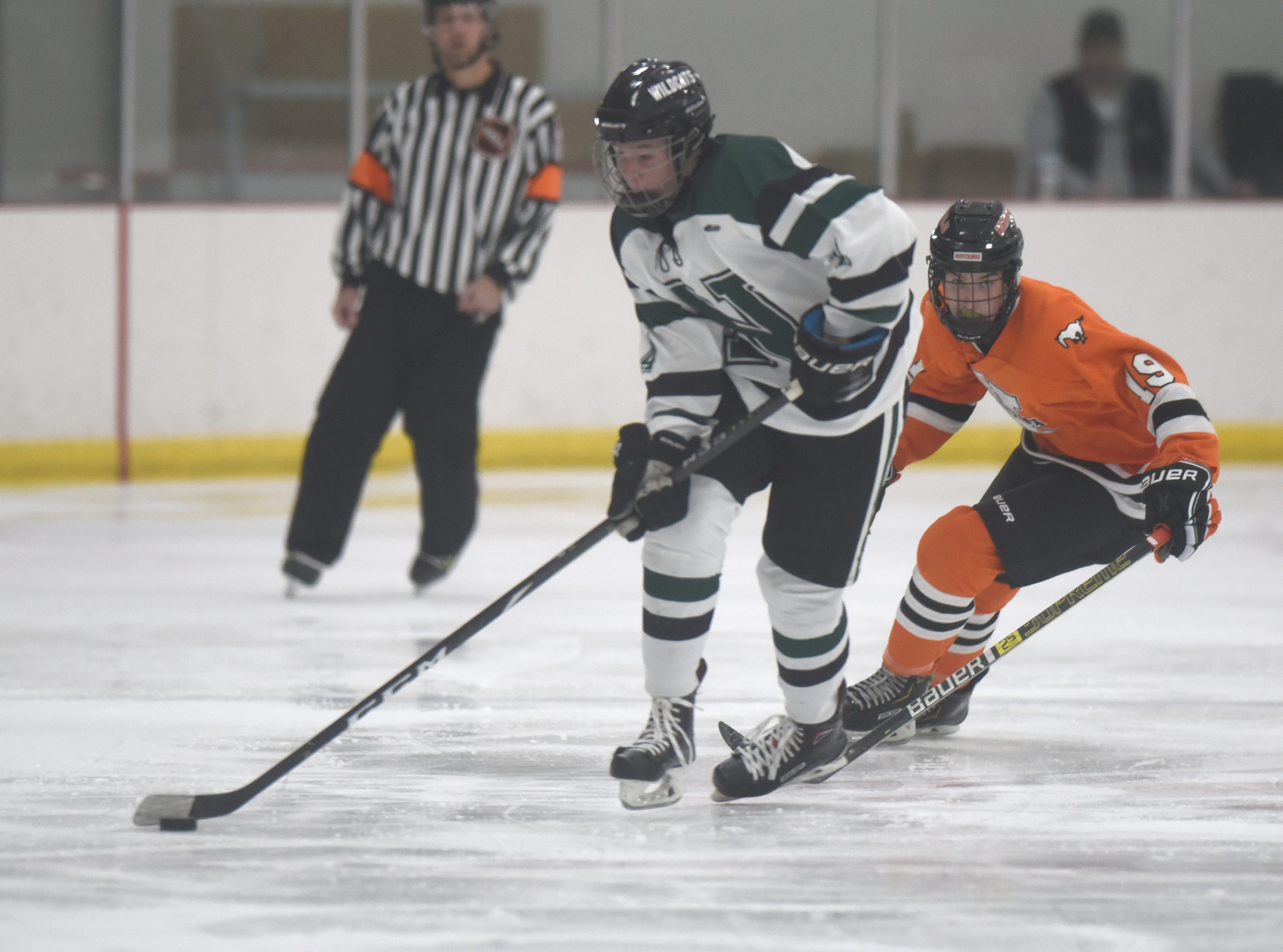 Novi defenseman Sam Lewinski (4) and Northville forward Jake McNeil (19) during a KLAA West match up between rivals Novi and Northville played at Novi Ice Arena Nov. 20, 2018.