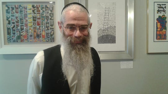 Rabbi Boruch Cohen stands in front of a art for sale at 36 Mystics.