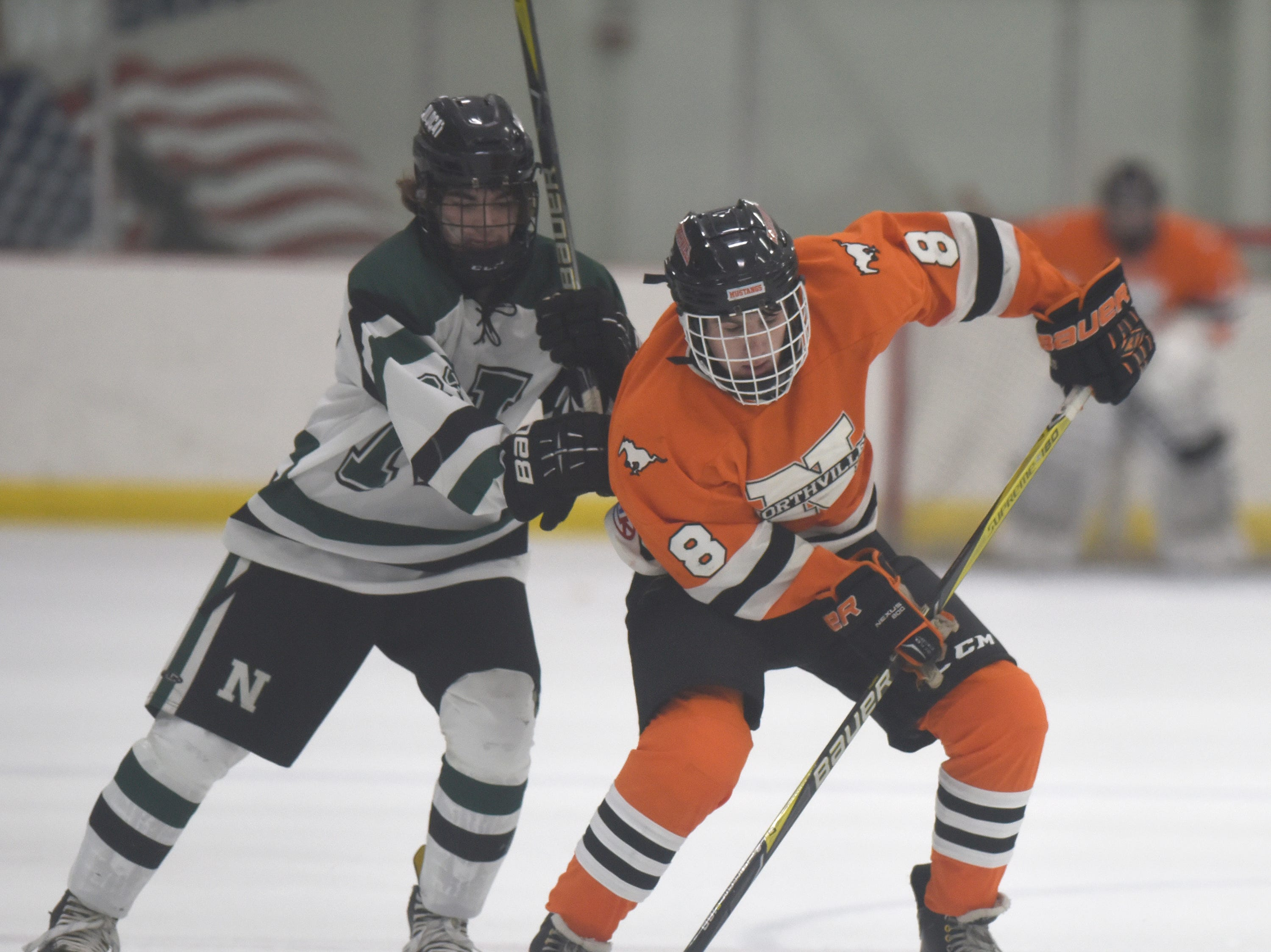 Novi forward Louis Wolff (23) and Northville forward Spencer Ziparo (8) during a KLAA West match up between the rivals played at Novi Ice Arena Nov. 20, 2018.