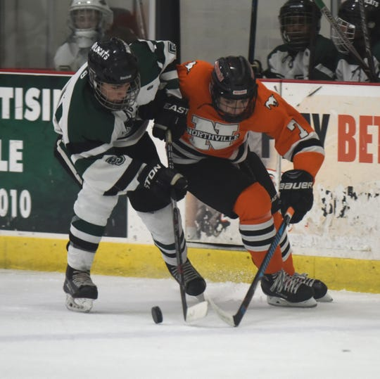 Novi defenseman Joey Vesche (5) and Northville forward Derek Fiebig (7) during a KLAA West match up between the rivals.
