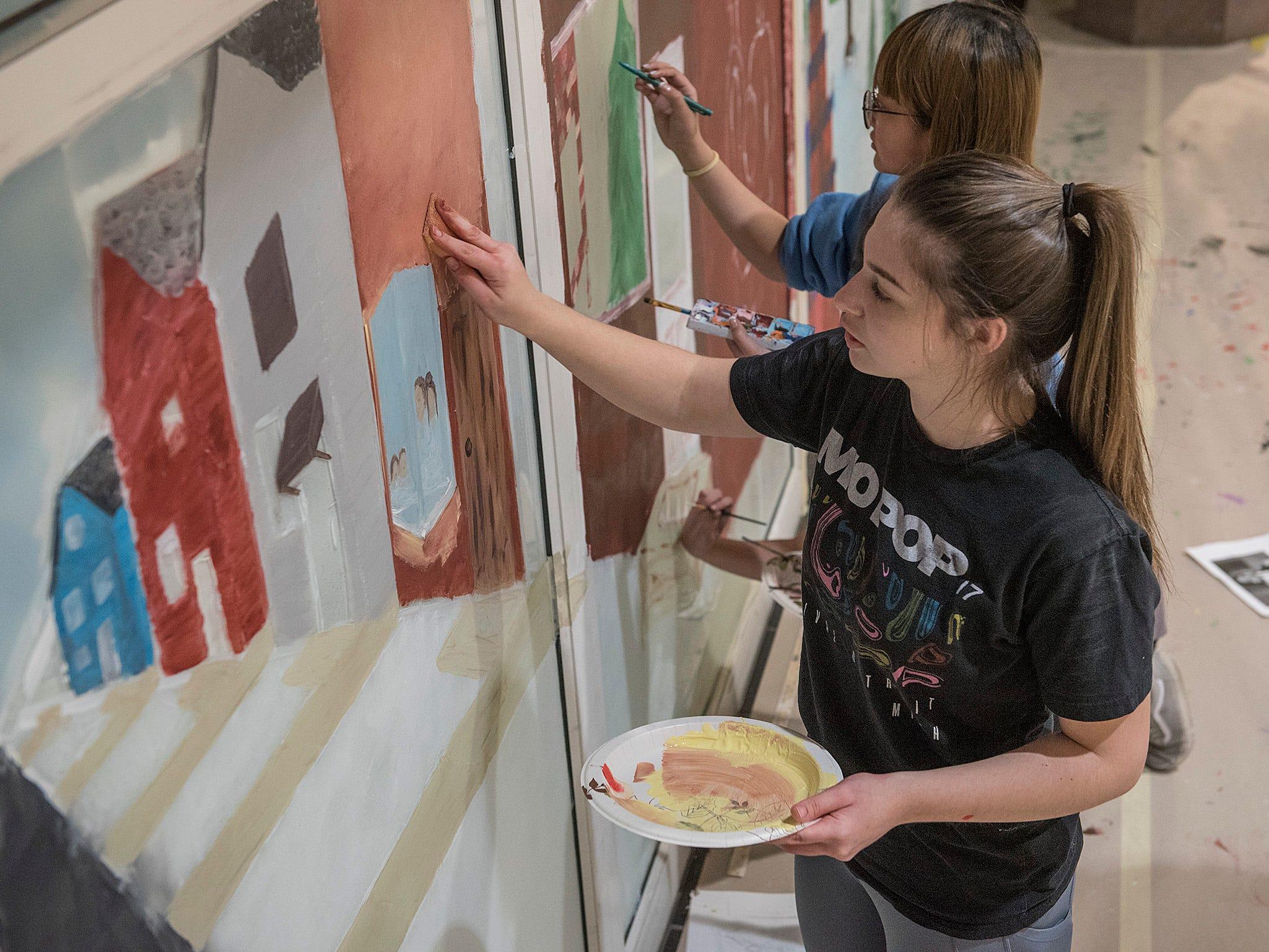 Stevenson senior Mackenzie M. Wilson, and freshman Cindy Doan, working on the holiday mural.