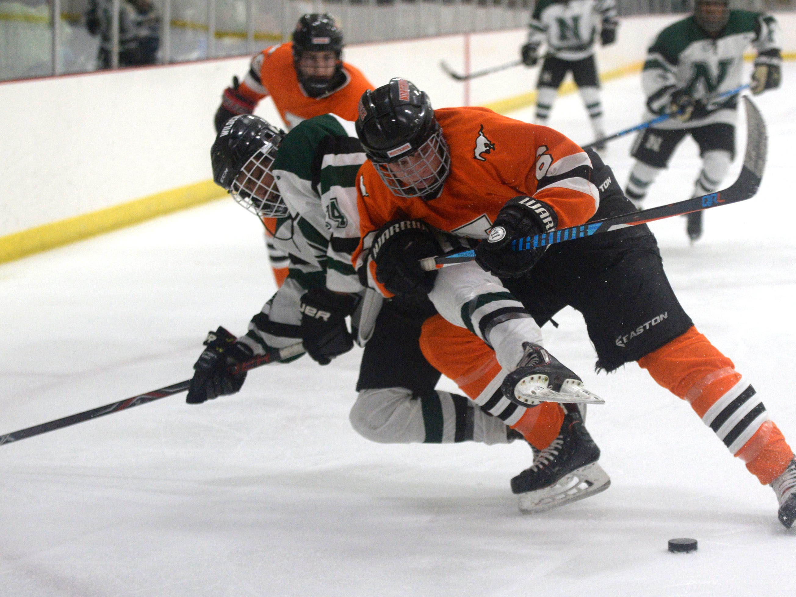Novi forward Jay Naidu (14) and Northville defenseman Ethan Collyer during a KLAA West match up played at Novi Ice Arena Nov. 20, 2018.