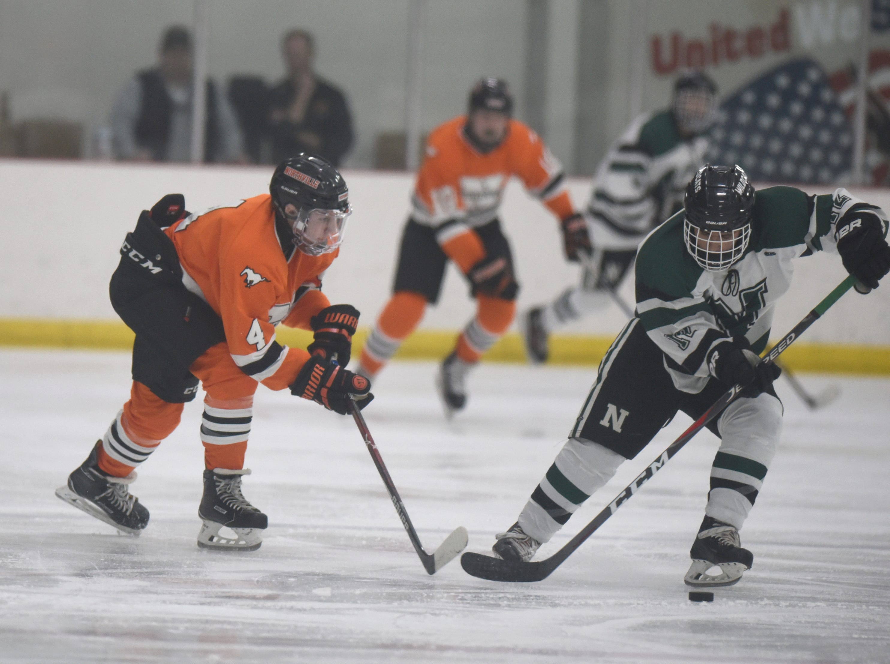 Northville defenseman Chris Bogenhagen (4) and Novi forward Maanas Sharma (12) during a KLAA West match up between rivals Novi and Northville played at Novi Ice Arena Nov. 20, 2018.