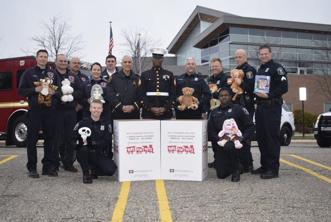 A group of Farmington Hills firefighters and police officers with Sgt. Michael Tatum representing the U.S. Marine Corps at the city's Toys for Tots kickoff event.