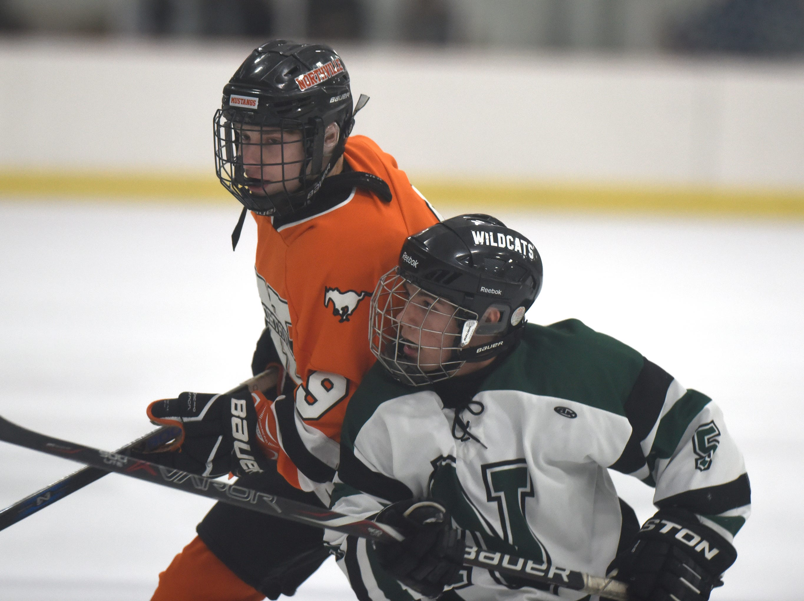 Northville forward Brett Dann (9) and Novi defenseman Joey Vesche (5) during a KLAA West match up between the rivals played at Novi Ice Arena Nov. 20, 2018.