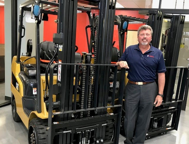 Fraza CEO Roger Runyan stands next to Caterpillar equipment in the company's lobby.