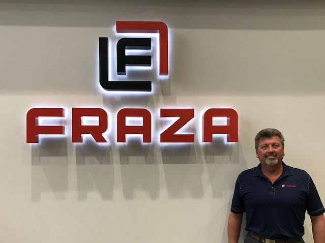 CEO Roger Runyan stands next to the new logo for Fraza in the company's lobby.