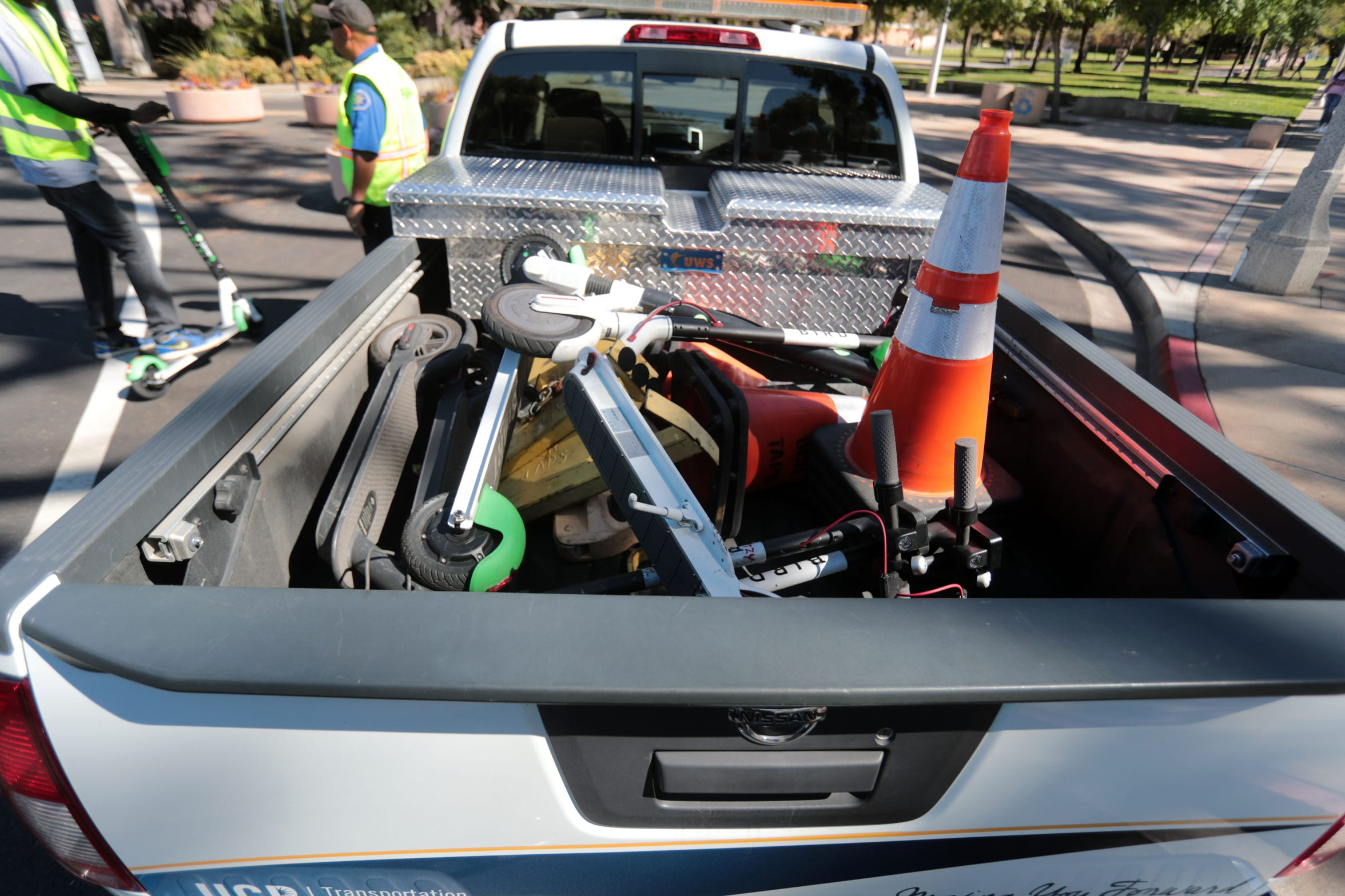 Lime and Bird electric scooters are confiscated by parking enforcement officials after being found scattered around the the University of California, Riverside, campus on Oct. 18, 2018.