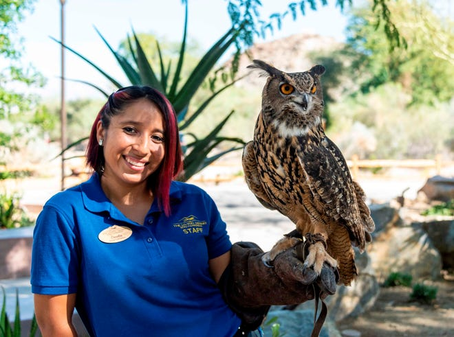 Animal Care Keeper, Claudia Garcia, poses with Bubo, the great horned owl