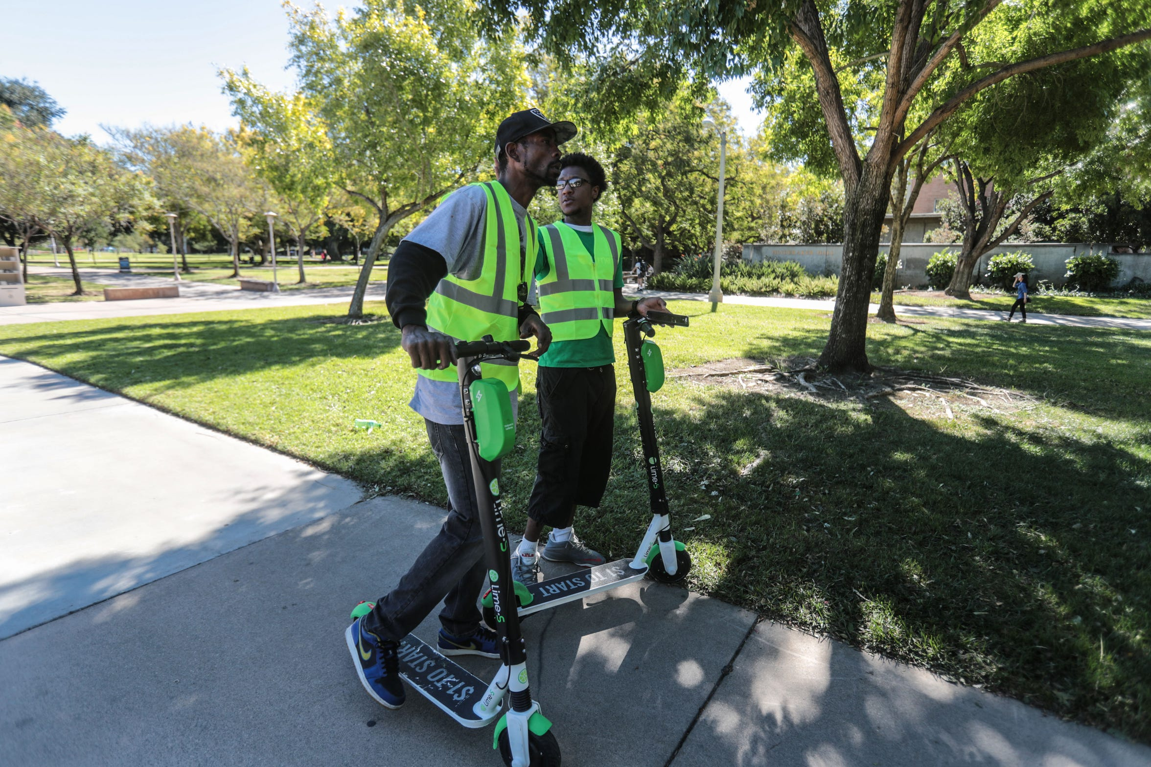 Trevor Carson and Omar Hill, both operators with Lime scooter company, look for scooters on the University of California, Riverside campus on Oct. 18, 2018. The two gather up the electric scooters to charge.