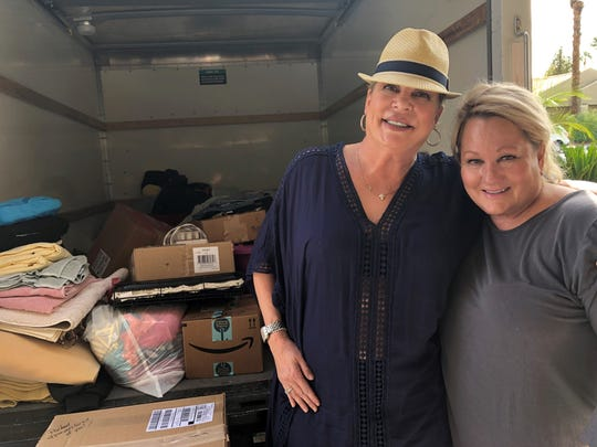 Sian Thiessen, 55, a medical laser  technician from Palm Desert, poses with her friend, Joan Palmtag, as they load a truck with donated items for victims of the Camp Fire.