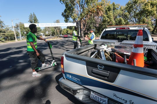 Trevor Carson and Omar Hill, both operators with Limes scooter company, talks to UC Riverside parking enforcement who has confiscated Bird and Lime scooters he found scatter on the UC Riverside campus on October 18, 2018.