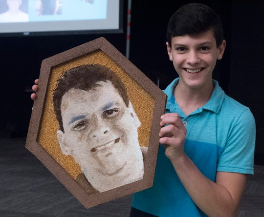 Payton Herrington shows off a portrait of his father, Bryan, made from seeds and other organic material on Tuesday, Nov. 20, 2018. The artwork will be included as part of the Donate Life float during the Rose Parade on Jan. 1, 2019.