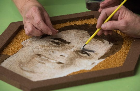 Family members of Bryan Herrington complete a portrait of the late Pensacola resident on Tuesday, Nov. 20, 2018. The artwork will be included as part of the Donate Life float during the Rose Parade on Jan. 1, 2019.