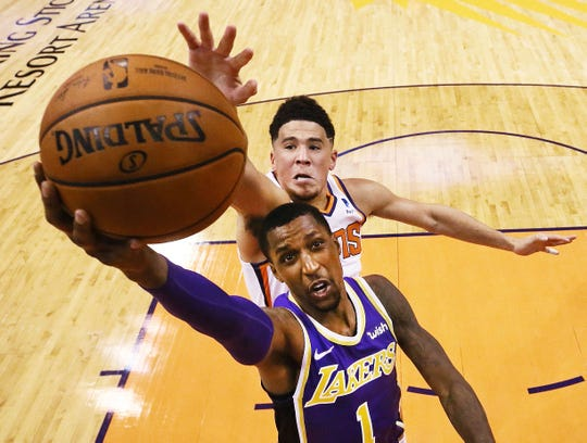 Los Angeles Lakers' Kentavious Caldwell-Pope dunks the ball against Phoenix Suns Devin Booker during a game on Oct. 24, 2018, at Talking Stick Resort Arena.