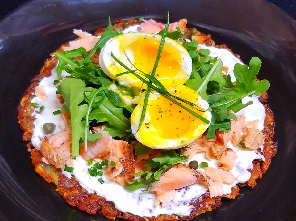 The French Connection: a potato tartin topped with two soft boiled eggs, capers, smoked salmon, cream cheese and fresh herbs .