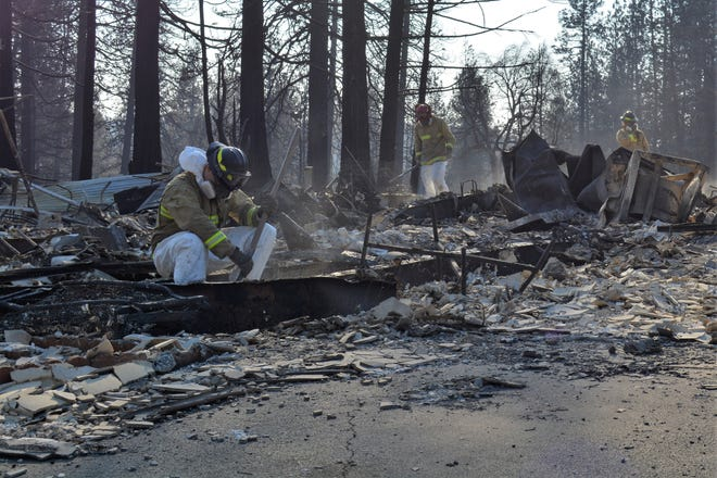 Firefighters with California Task Force 4, a FEMA-sponsored urban search and rescue group based in Oakland, search Tuesday, Nov. 20, 2018, through the rubble of trailers destroyed by the Camp Fire. Crews conducted secondary searches ahead of heavy rains forecast later in the week.