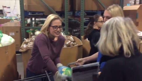 Sen.-elect Kyrsten Sinema hands out turkeys at Desert Mission Food Bank in Phoenix the day before Thanksgiving, Nov. 21, 2018.