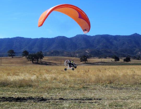 A motorized paraglider comes in for a landing near Santa Margarita, California.