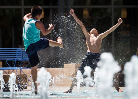 Drayden Gloria, 9, Phoenix, left, kicks water at his brother, Adriel, 10, on the splash pad at Cityscape in Phoenix, Tuesday, May 29, 2018.