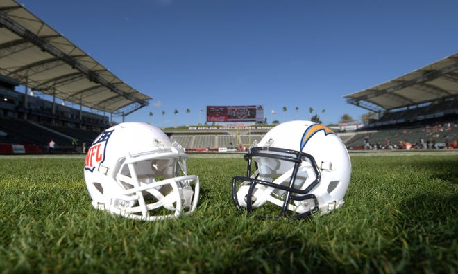 An NFL shield logo helmet and Los Angeles Chargers helmet sit on the grass at StubHub Center on Jan. 21, 2017.
