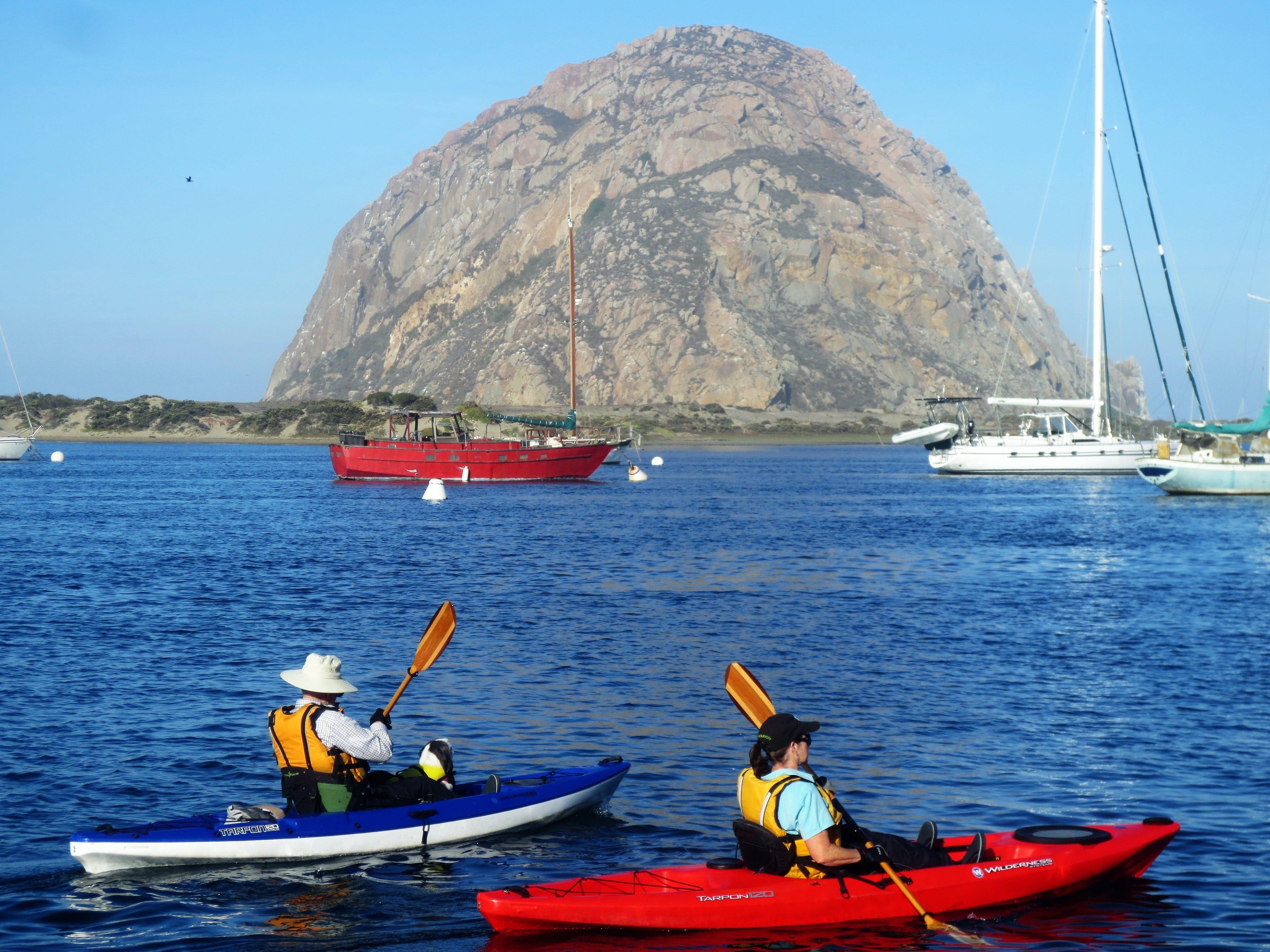 Kayakers paddle past Morro Rock in San Luis Obispo County, California.