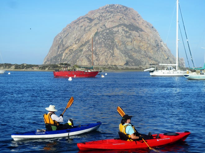 Kayakers paddle past Morro Rock in San Luis Obispo County, California.