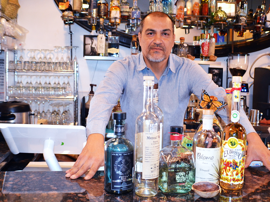 Francisco Peralta, who helps run El Charro Hipster Bar & Cafe with his family, shows off his artisanal mezcal collection.