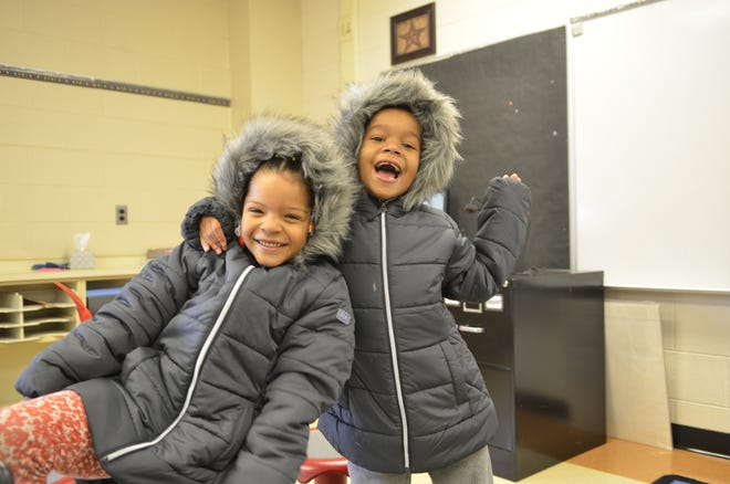 First graders Jolie Abayan-Kuadio, left, and Lexi Arnone, received coats donated by DTE to the Literacy Academy at Cleveland Elementary.