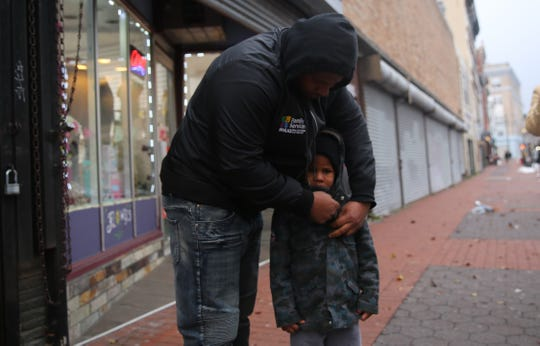 Yahya Archer helps his son, Praise, with the hood of his jacket as the two stand on Main Street during a shooting response event in the city of Poughkeepsie on Wednesday. He said the recent string of shootings in the city has left him feeling the community has a lot more work to do.