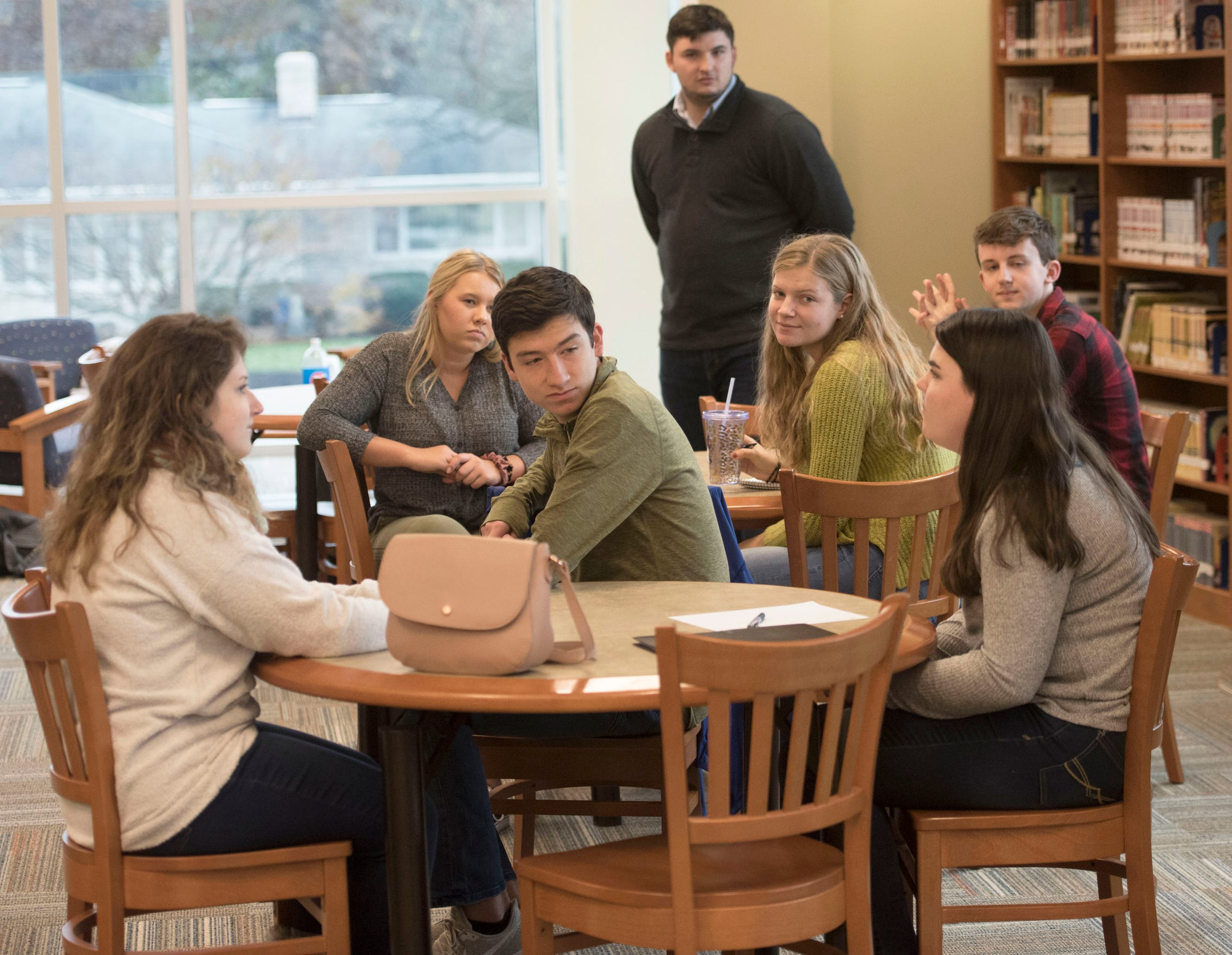 Kelton Chastulik, standing, is joined by other CASHS alumni and current students as they coordinate a book drive for Franklin County Homeless Shelter on Wednesday, November 21, 2018. Chastulik is currently a student at Princeton University.