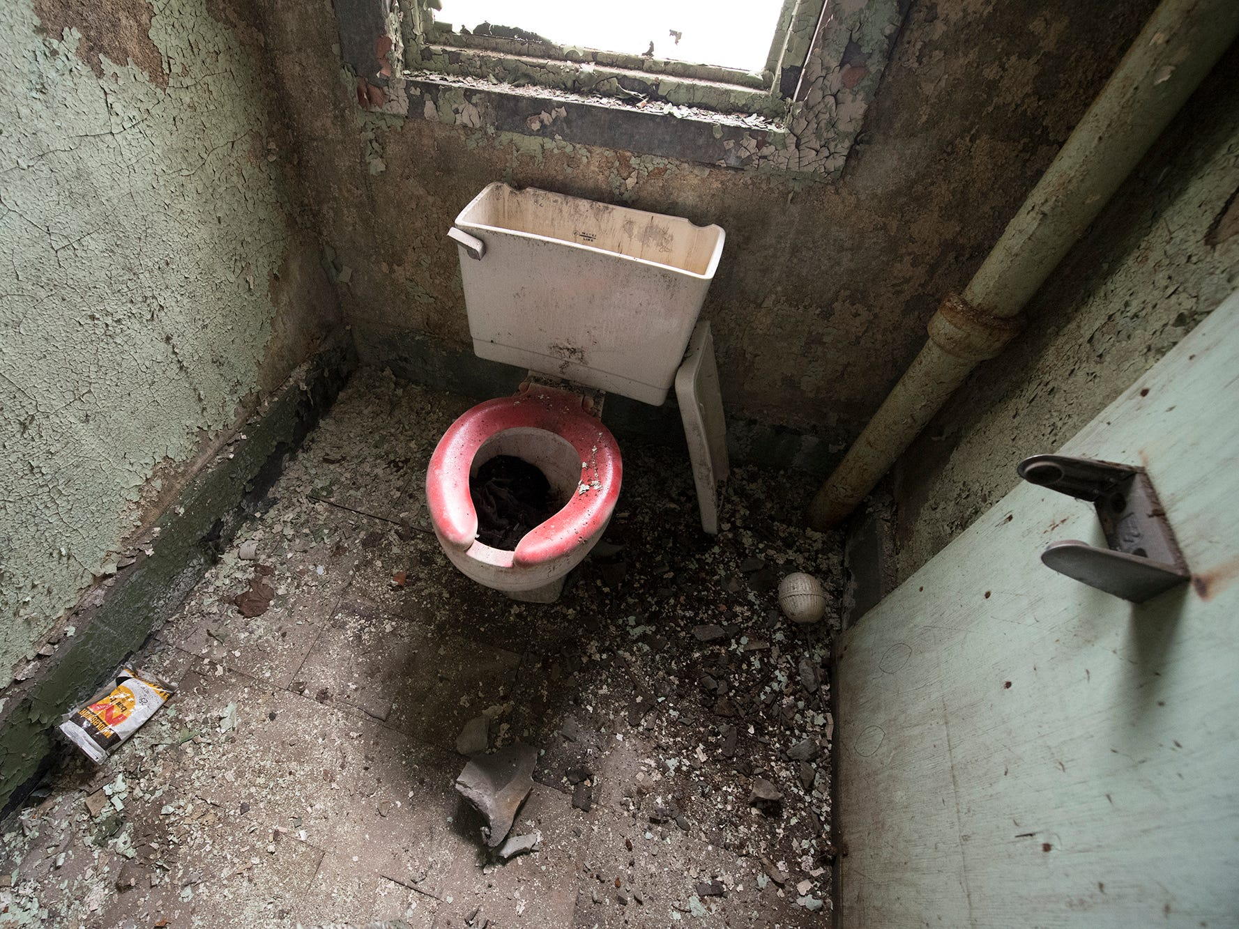 A toilet is subjected to the elements from a broken window inside the old York County Prison.