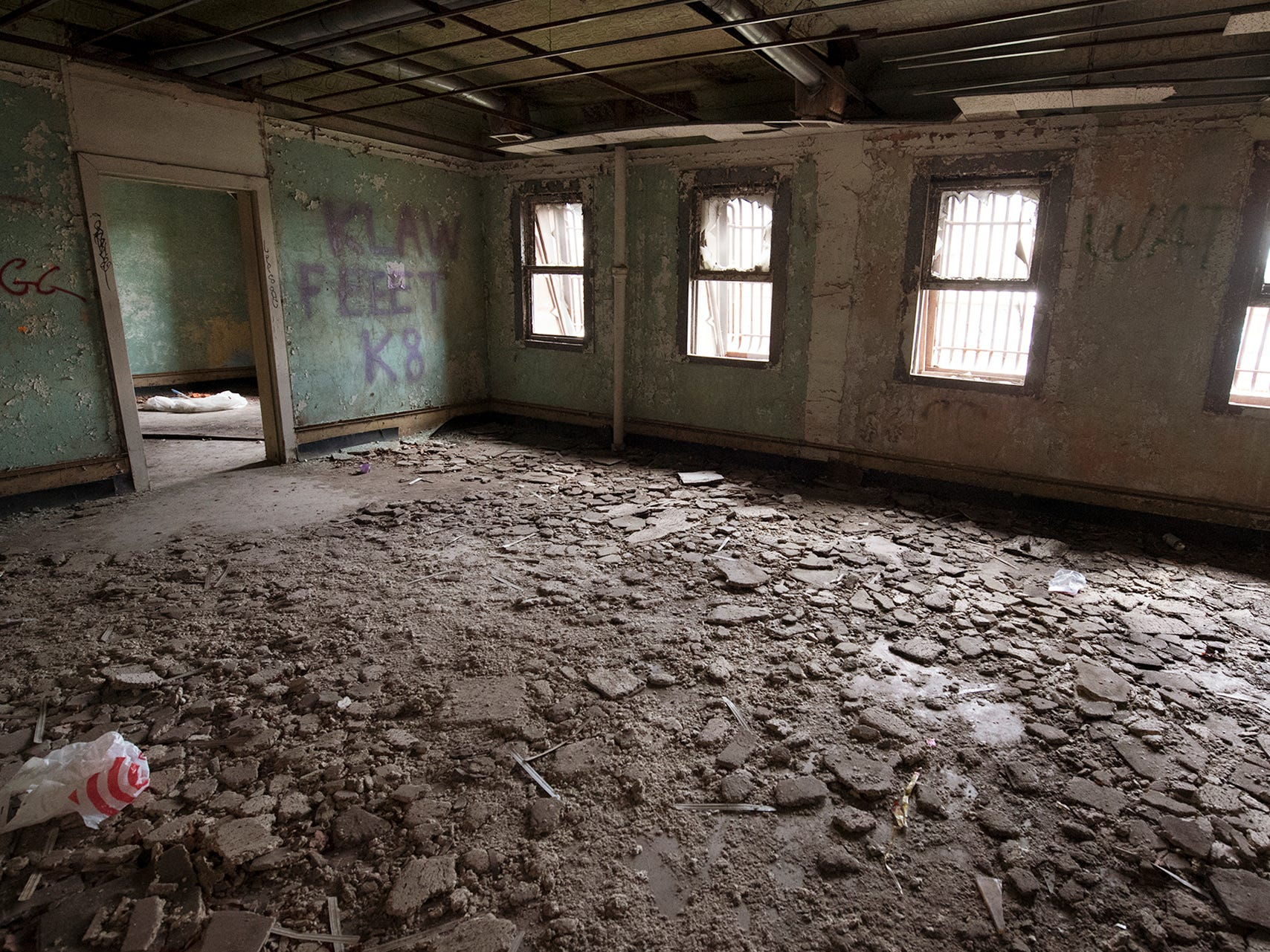Ceiling tiles are crumbled on the floor of first-floor office space inside the old York County Prison.