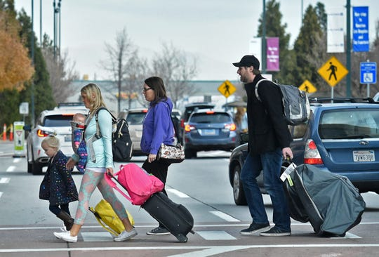 Travelers cross the street at Reno-Tahoe International Airport on Wednesday, Nov. 21, 2018. Airport officials estimate 80,000 travelers will go through the airport the seven days surrounding Thanksgiving.