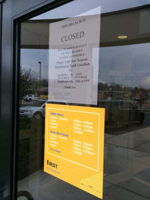 "A sign posted on the door to First Financial Bank announces the bank was closed Wednesday afternoon ""due to an emergency."""