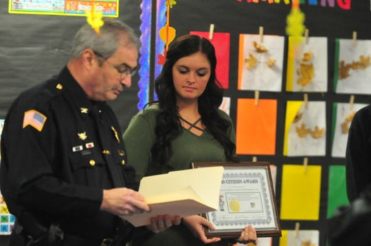 Chief Jim Branum presents teacher Allison Gray with a Good Citizen Award for her kindergarten class because of the way the students handled finding what turned out to be a toy gun on the playground.