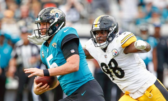 Jacksonville Jaguars quarterback Blake Bortles (5) runs the ball as Pittsburgh Steelers inside linebacker Vince Williams (98) closes in.