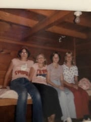 Lolene Rios, left, and Marge Nelms, second to left, sit with two other girls on a bunk while at camp in 1977.